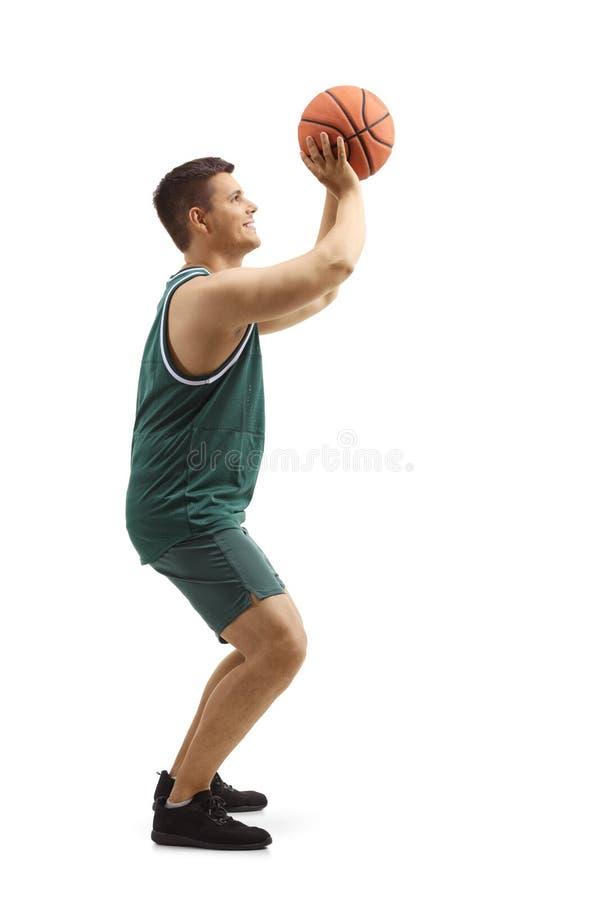 Hombre en un jersey de los deportes que tira con un baloncesto fotos de archivo libres de regalías
