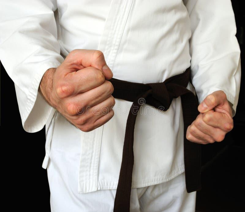 Hombre en un kimono y una correa para los artes marciales fotos de archivo
