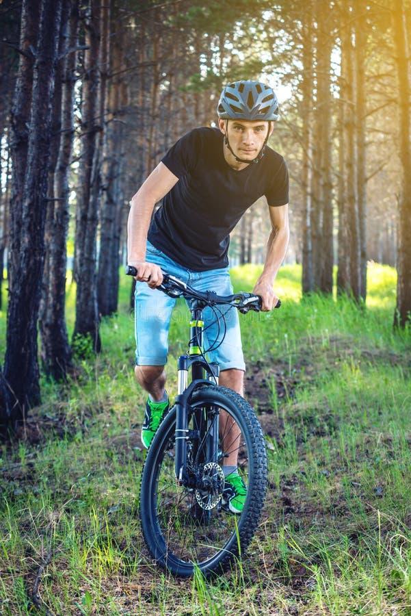 Hombre en un montar a caballo del casco en una bici de montaña en el bosque entre los árboles Ciclista en el movimiento Forma de  fotos de archivo