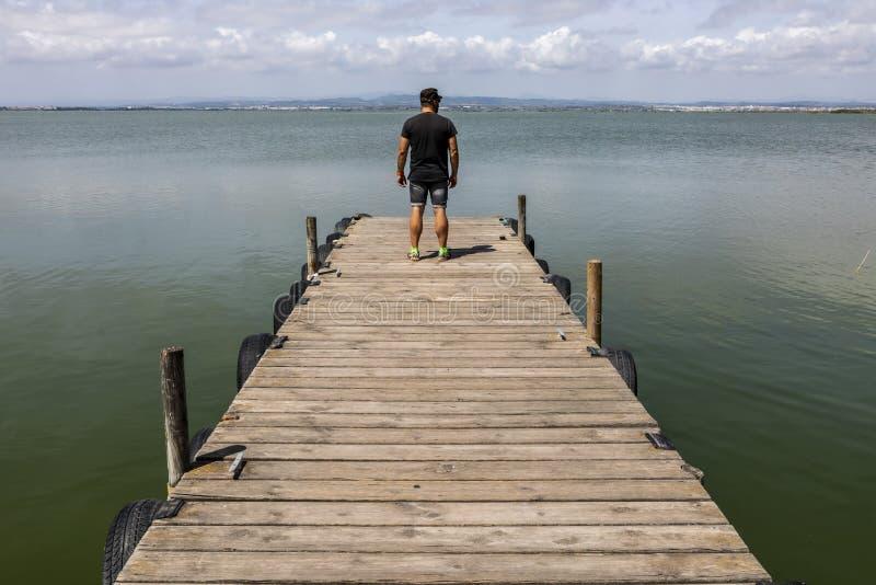 Hombre en un muelle por el lago en el cielo de la mañana imágenes de archivo libres de regalías
