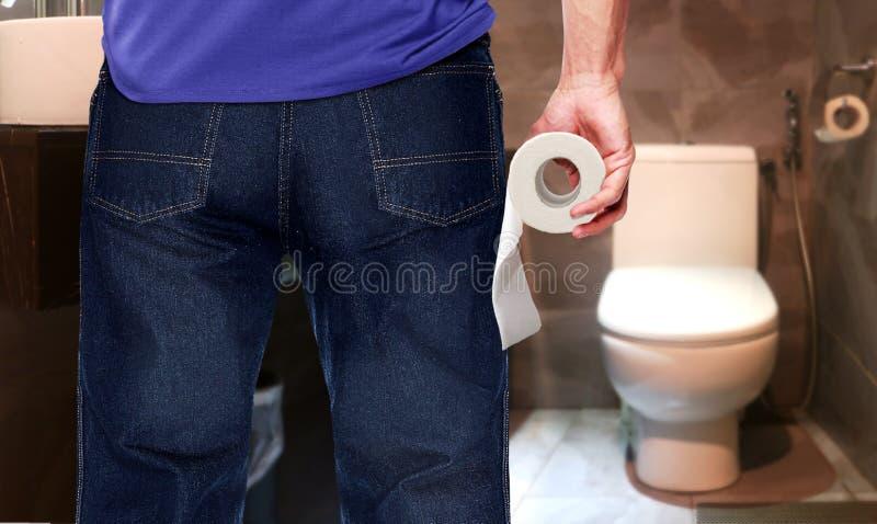Hombre en un retrete que lleva a cabo el rollo del papel seda imagen de archivo