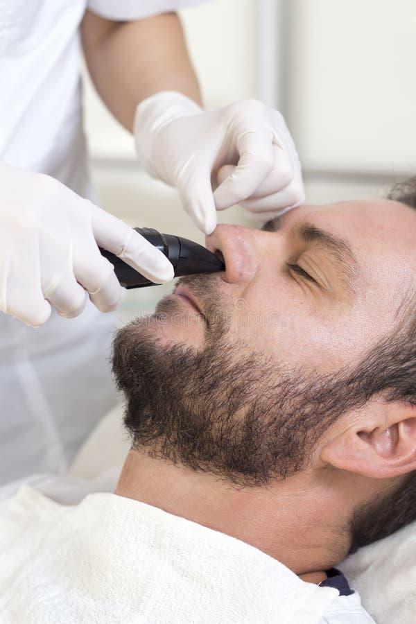 Hombre en un salón de belleza durante una cirugía del retiro del pelo de nariz imagen de archivo libre de regalías