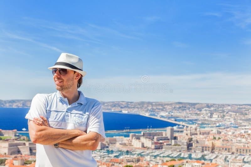 Hombre en un sombrero y las gafas de sol que presentan contra la ciudad de Marsella imagen de archivo libre de regalías
