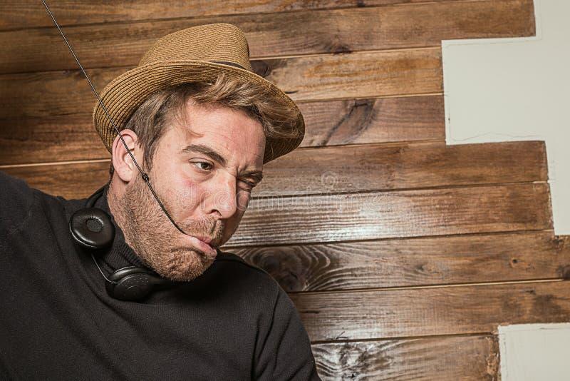Hombre en un sombrero y los auriculares que hacen caras divertidas imagen de archivo libre de regalías