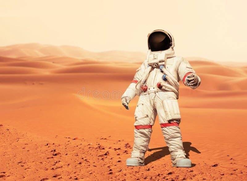 Hombre en un traje de espacio que se coloca en el planeta rojo Marte astronauta fotos de archivo