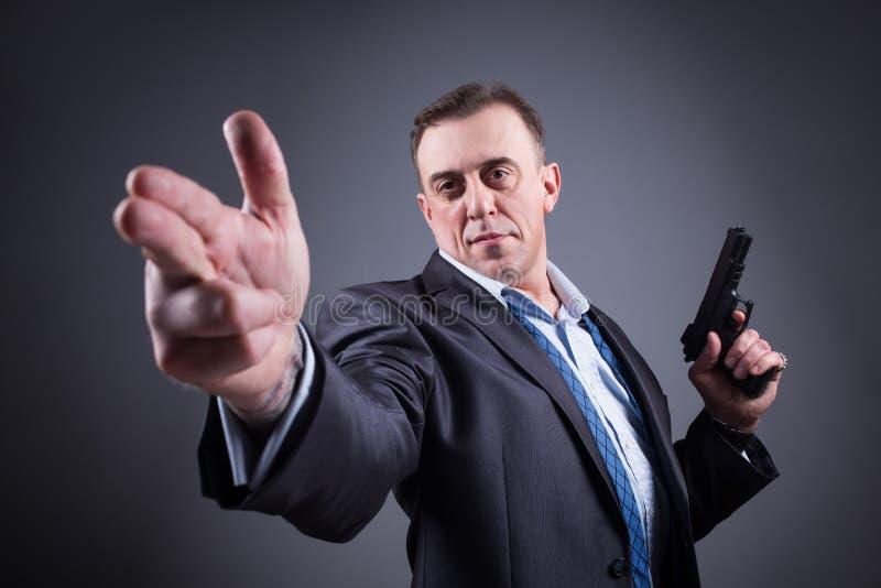 Hombre en un traje de negocios con un arma fotos de archivo libres de regalías