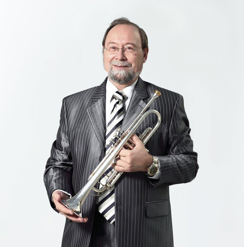 Hombre en un traje gris con una trompeta imagenes de archivo