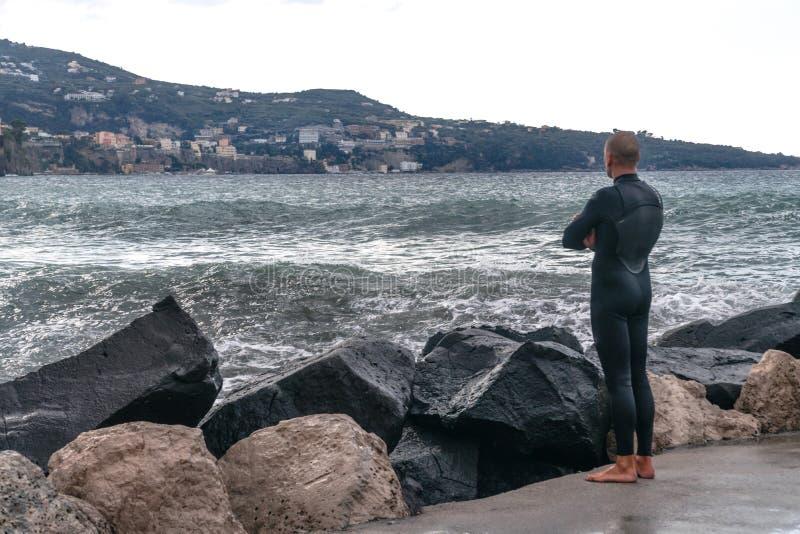 Hombre en un traje mojado, persona que practica surf, colocándose en la orilla y mirando las ondas en el fondo de la montaña, Sor fotos de archivo