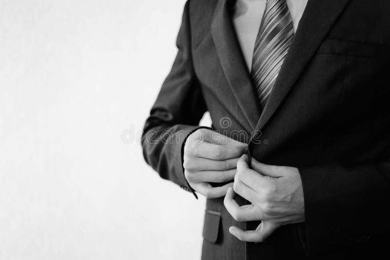 Hombre en un traje negro clásico con una situación más butanier en la ventana imagenes de archivo