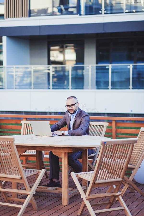 Hombre en un traje que se sienta con un ordenador portátil foto de archivo