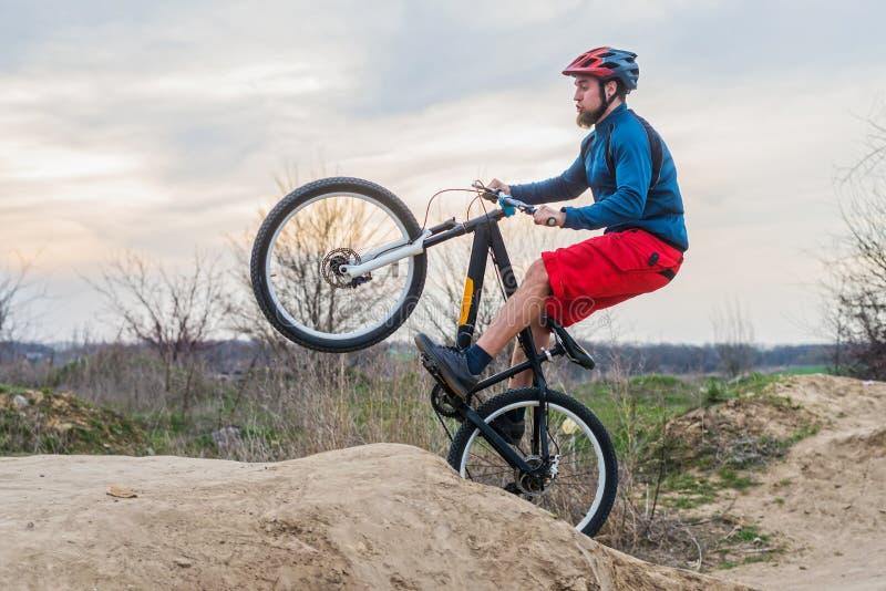 Hombre en una bici de montaña en pantalones cortos rojos y el suéter azul que realizan un salto de la suciedad Forma de vida acti fotos de archivo libres de regalías