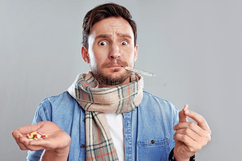 Hombre en una bufanda que sostiene el termómetro y una mano llena de píldoras aisladas en un fondo blanco fotos de archivo libres de regalías