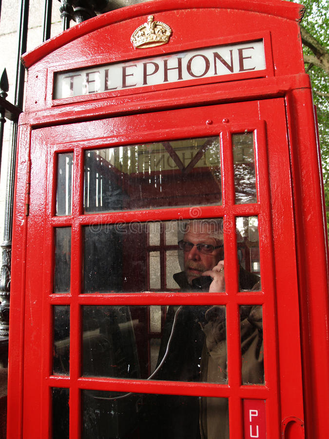 Hombre en una cabina de teléfono roja, Londres imagenes de archivo