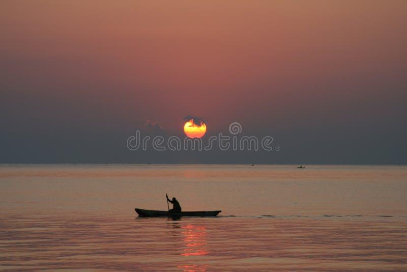Hombre en una canoa en la salida del sol imagen de archivo
