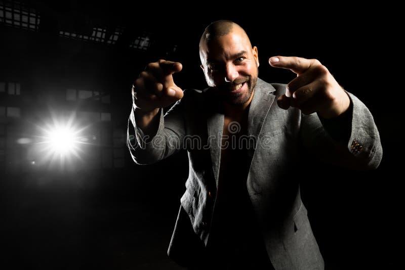 Hombre en una chaqueta en un cuarto oscuro imagenes de archivo