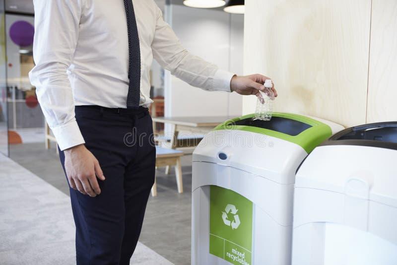 Hombre en una oficina que lanza la botella plástica en la papelera de reciclaje imagenes de archivo