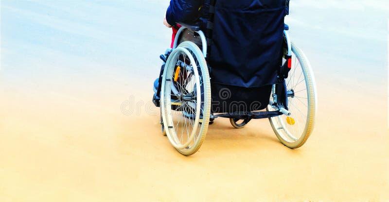 Hombre en una silla de ruedas mientras que camina la calle tono, vista posterior fotos de archivo