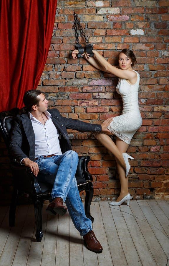 Hombre en una silla y la mujer en grillos en el cuarto fotos de archivo