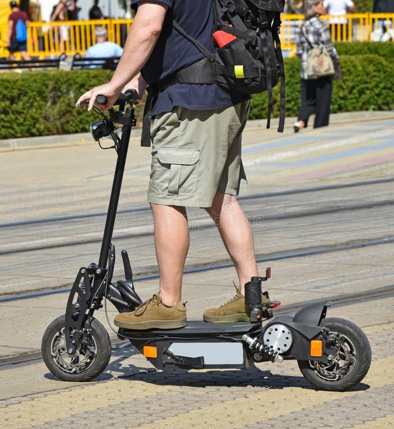 Hombre en una vespa eléctrica en la calle de la ciudad fotografía de archivo libre de regalías