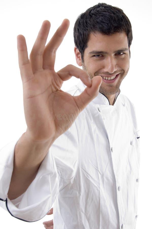 Hombre en uniforme del cocinero con la muestra aceptable imagenes de archivo
