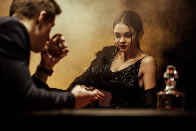 Hombre en whisky de consumición del traje mientras que juega el póker con la mujer hermosa fotografía de archivo