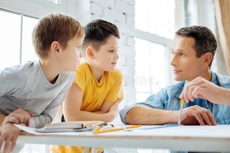 Hombre encantador que comunica con los niños mientras que trabaja imagen de archivo libre de regalías
