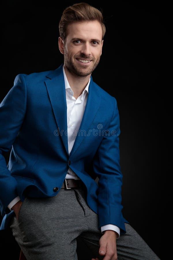 Hombre encantador que lleva a cabo su mano en su bolsillo y sonrisa foto de archivo libre de regalías