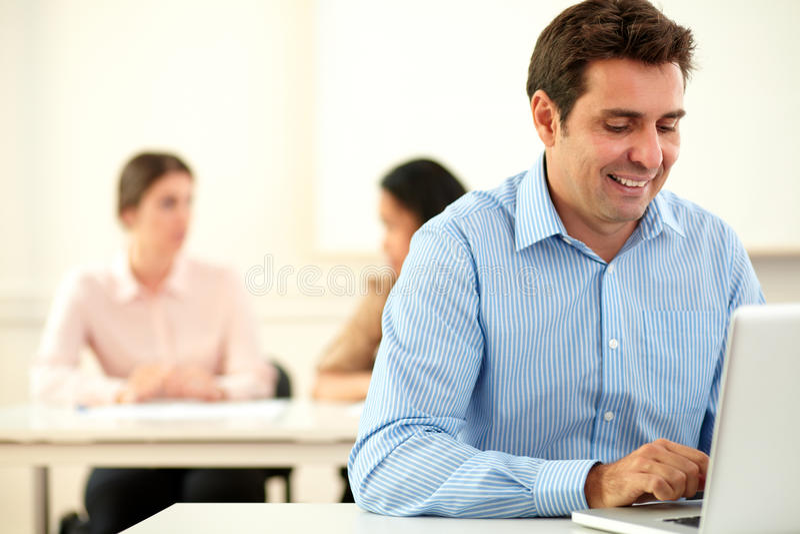 Hombre encantador que trabaja en su ordenador portátil mientras que se sienta foto de archivo libre de regalías