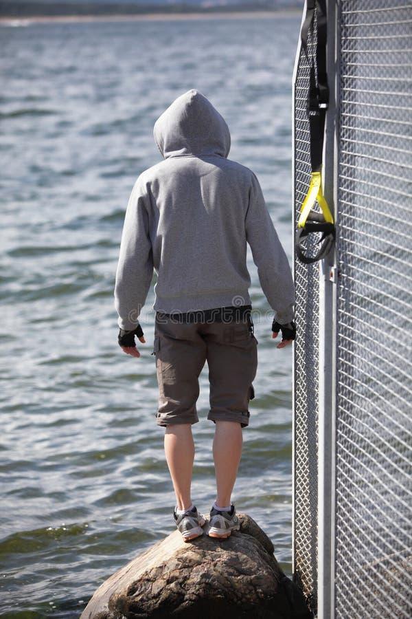 Hombre encapuchado antes de al aire libre, entrenamiento de la suspensión en el mar fotos de archivo