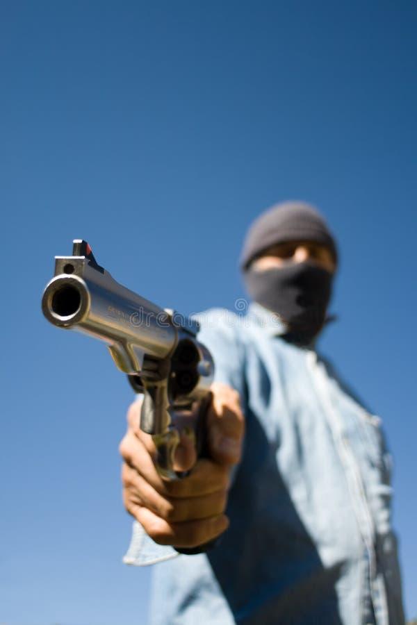 Hombre encapuchado con amenazar de la arma de mano de 44 botellas dobles imagen de archivo