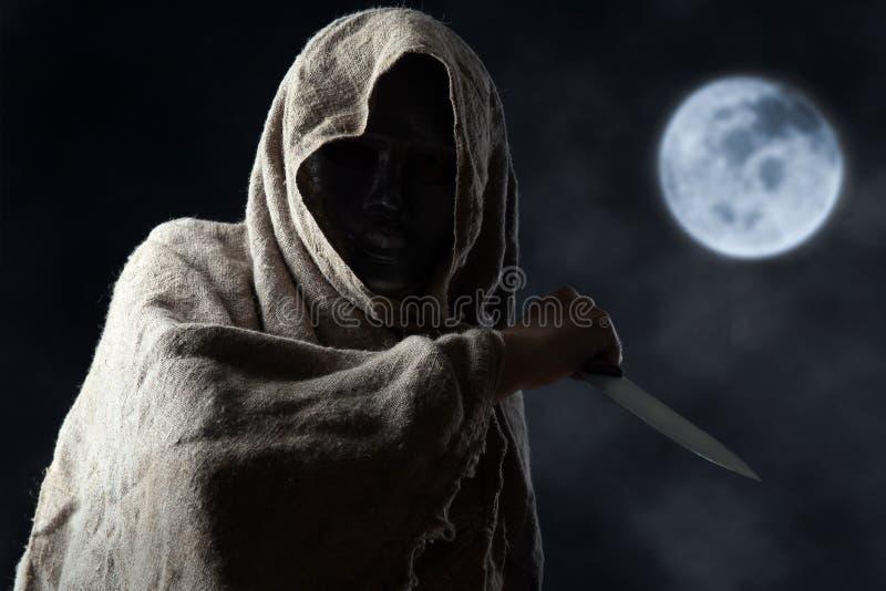 Hombre encapuchado en máscara con el cuchillo foto de archivo libre de regalías