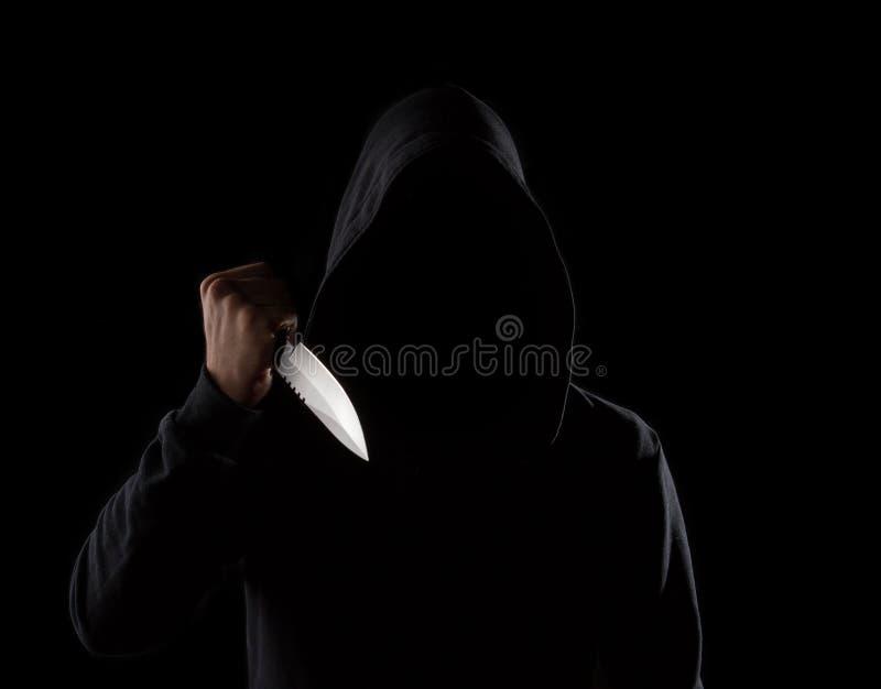 Hombre encapuchado peligroso que sostiene el cuchillo fotografía de archivo