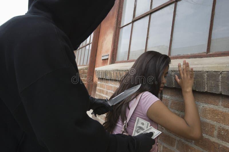 Hombre encapuchado que roba a la mujer joven con el cuchillo fotos de archivo libres de regalías