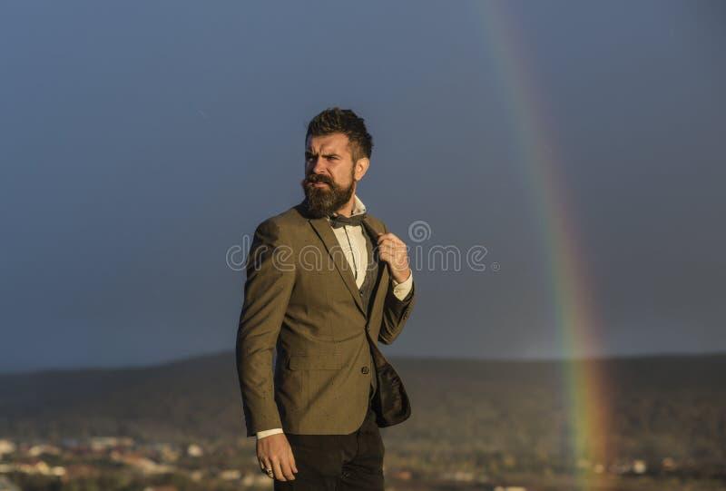 Hombre encima de la roca y del arco iris imagen de archivo