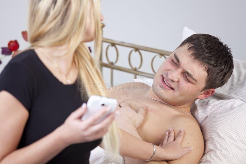 Hombre enfermo con el dolor en cama foto de archivo