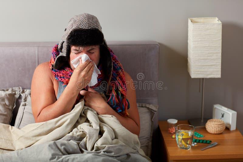 Hombre enfermo con la mentira fría en nariz de la cama y del soplo fotos de archivo