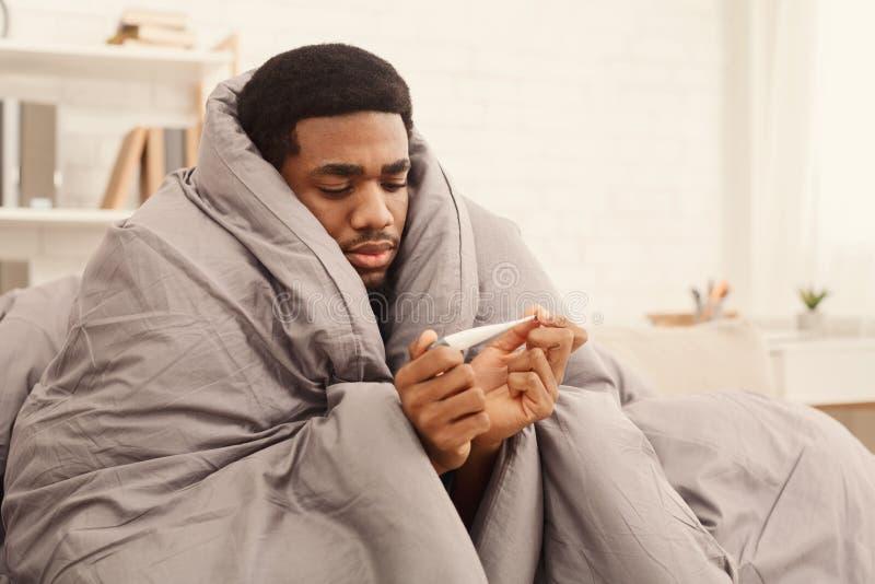 Hombre enfermo cubierto con el termómetro que se sostiene combinado fotografía de archivo libre de regalías