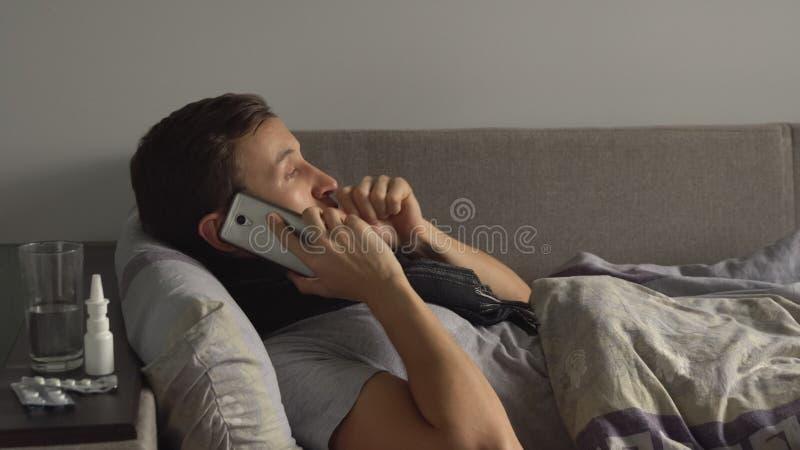 Hombre enfermo en cama al lado de sus medicaciones en su hogar que habla en el teléfono Virus sufridor de la gripe del frío y del foto de archivo