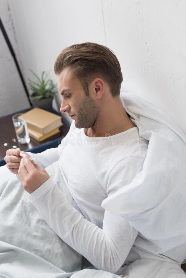 Hombre enfermo hermoso que mira rato del termómetro foto de archivo libre de regalías