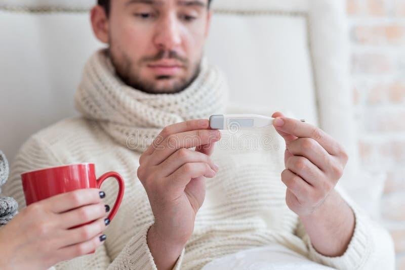Hombre enfermo infeliz que tiene una fiebre imágenes de archivo libres de regalías