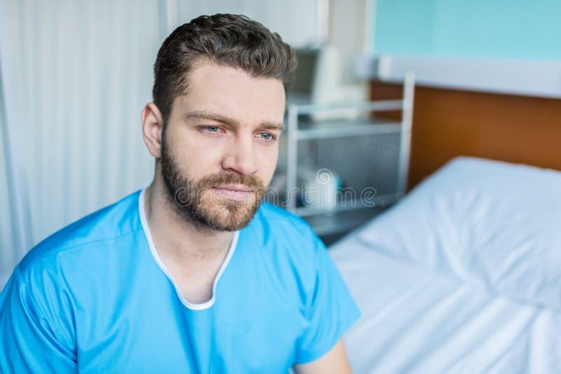 Hombre enfermo joven que se sienta en cama de hospital, paciente de la cama de hospital imágenes de archivo libres de regalías