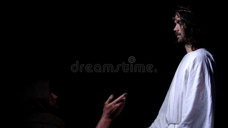Hombre enfermo pobre en traje que pide a Jesús en la corona de las espinas misericordia y que bendice fotos de archivo