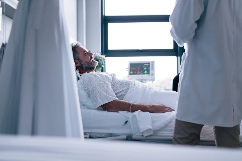 Hombre enfermo que miente en cama de hospital con el doctor imagenes de archivo