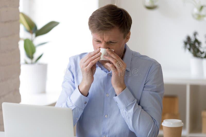 Hombre enfermo que se sienta en la oficina y la nariz de funcionamiento del estornudo imagen de archivo libre de regalías