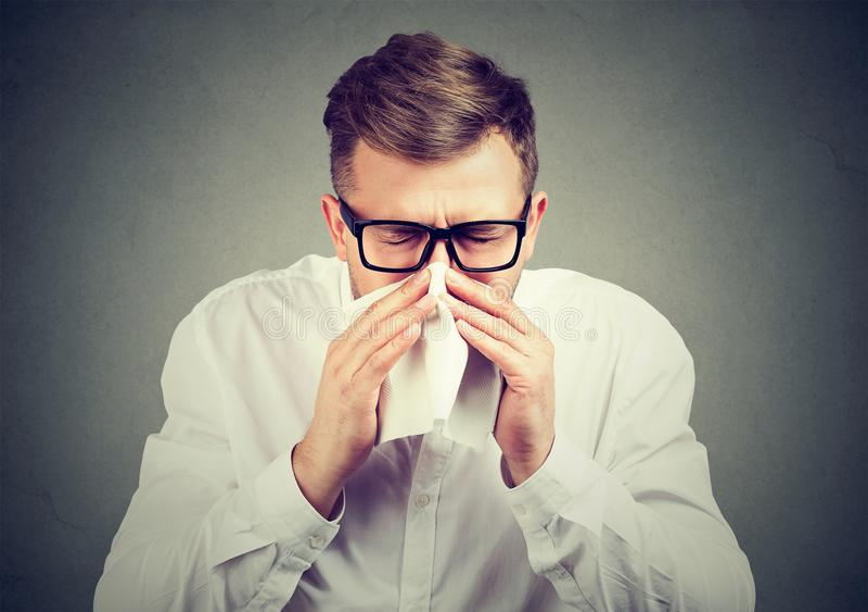Hombre enfermo que tiene gripe que estornuda foto de archivo libre de regalías