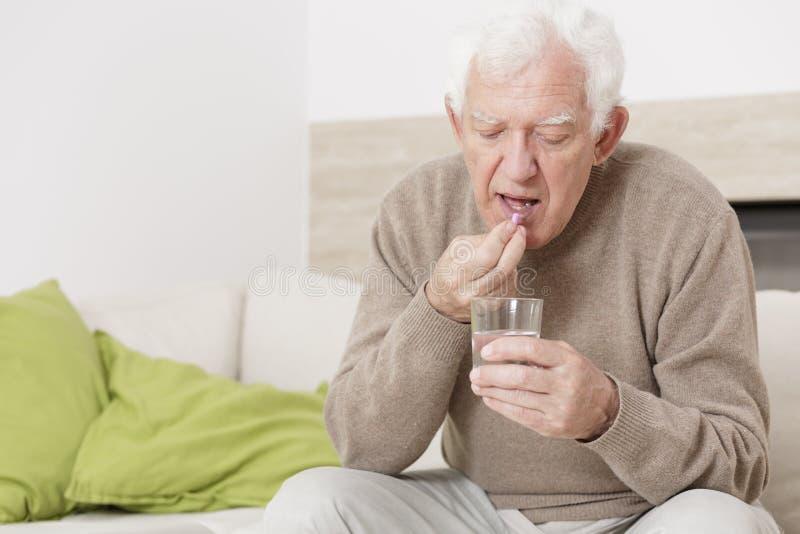 Hombre enfermo que toma la medicina imagen de archivo