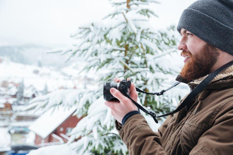 Hombre enfocado que usa la cámara y tomando las fotos en invierno foto de archivo libre de regalías