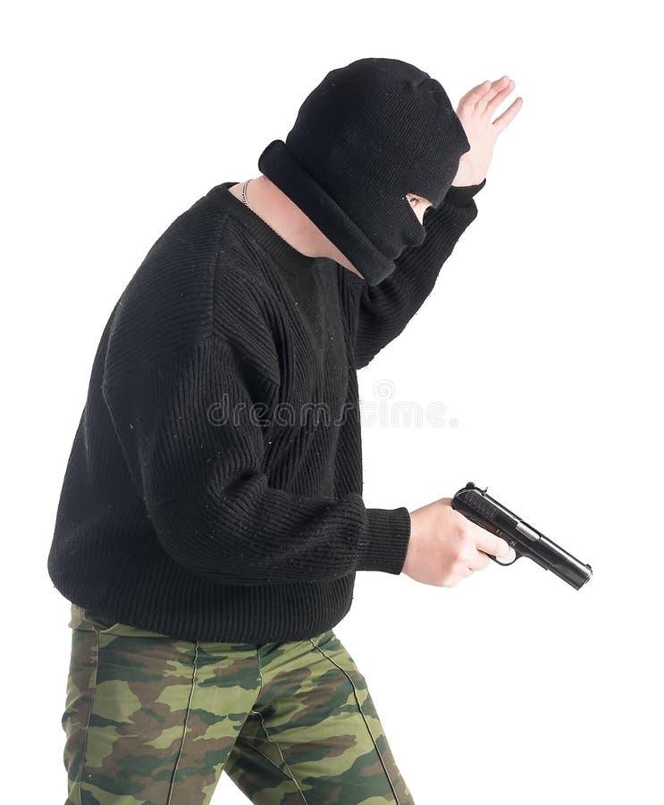 Hombre enmascarado con el arma foto de archivo