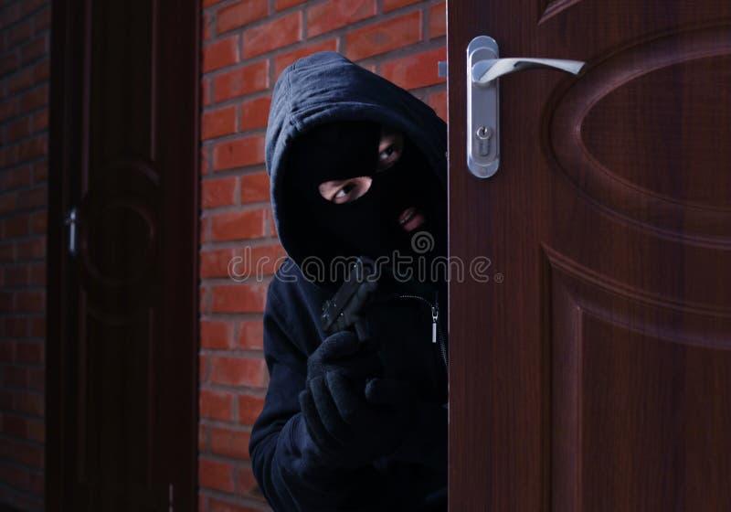 Hombre enmascarado con el arma que espía detrás de puerta abierta Delito imagenes de archivo