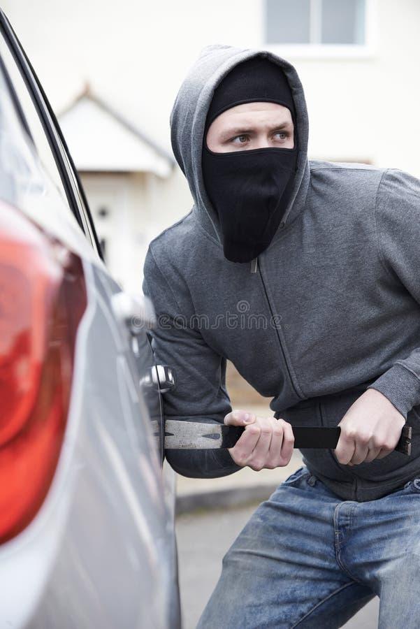 Hombre enmascarado que se rompe en el coche con la palanca imagen de archivo libre de regalías
